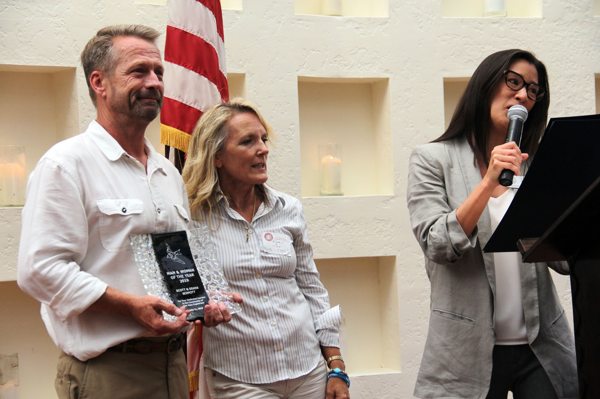 Representing Congressman Mike Levin's office, Cindy Gitter (far right) presents the San Juan Capistrano Chamber of Commerce's Man and Woman of the Year Award to Scott and Diana Schmitt during the Annual Installation and Awards Banquet on Thursday, July 11. Photo Shawn Raymundo