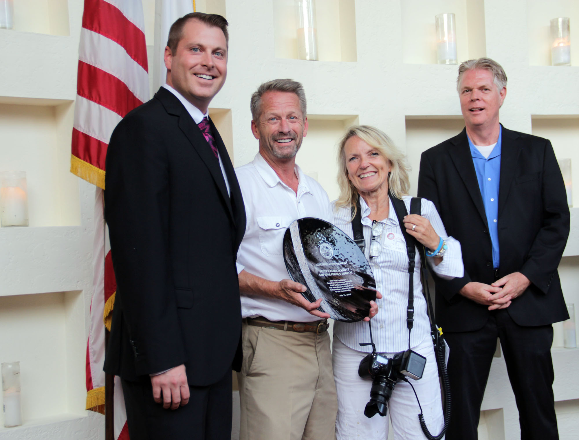 San Juan Capistrano Chamber of Commerce CEO George Peppas III (far left) presents the Lifetime Achievement Award to Scott and Diana Schmitt alongside Jim Taylor on July 11. Photo: Shawn Raymundo