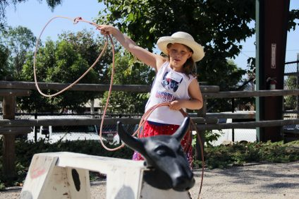 With her eye on the fake steer's horns, Lucy Kurtenacker swings about her lasso as she prepares to release it. Photo: Shawn Raymundo
