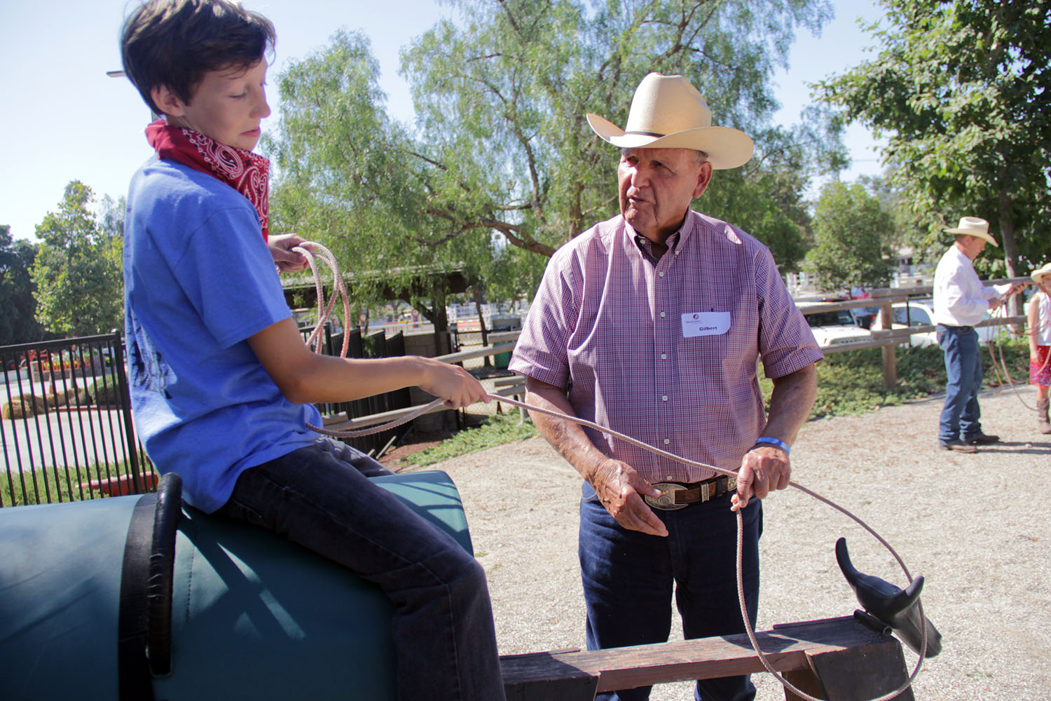 After successfully getting his lasso around the fake steer's horns, Soren Olsen admires his throwing skills while Gilbert Aguiree, executive vice president of ranch operations at Rancho Mission Viejo, offers words of praise. Photo: Shawn Raymundo