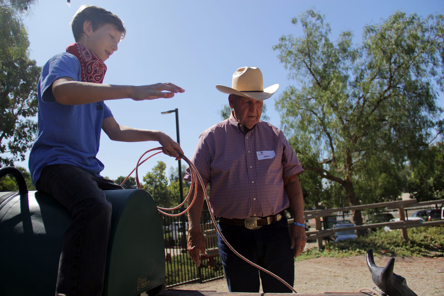 Soren Olsen lassos a fake steer with Gilbert Aguiree, executive vice president of ranch operations at Rancho Mission Viejo, standing by to offer pointers during the Shea Center's annual Cowboy Camp on Wednesday, Aug. 14. Photo: Shawn Raymundo