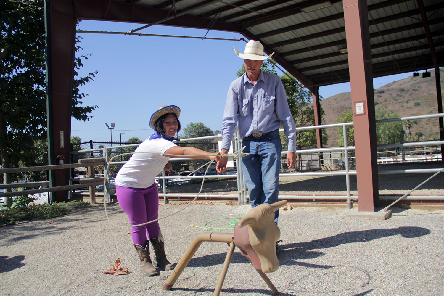 With Brent Freese as her teacher, Makena Lee takes aim while attempting to lasso the horns of a fake steer at the Shea Center's annual Cowboy Camp. Photo: Shawn Raymundo
