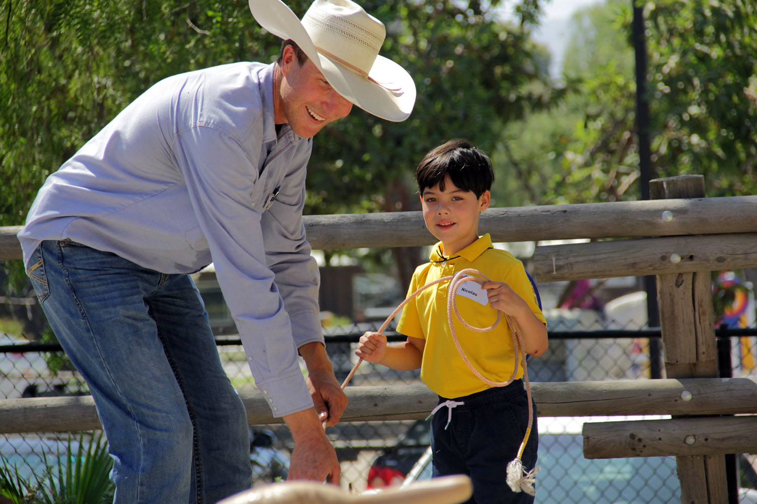 Brent Freese shows Nicolas Fellner how to tighten the rope after lassoing a fake steer. Photo: Shawn Raymundo